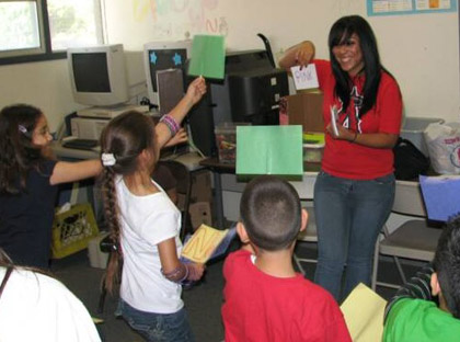 Picture of ELACYC children enjoying the goofy grammar game, led by Cal State L.A. student Tania Varona.