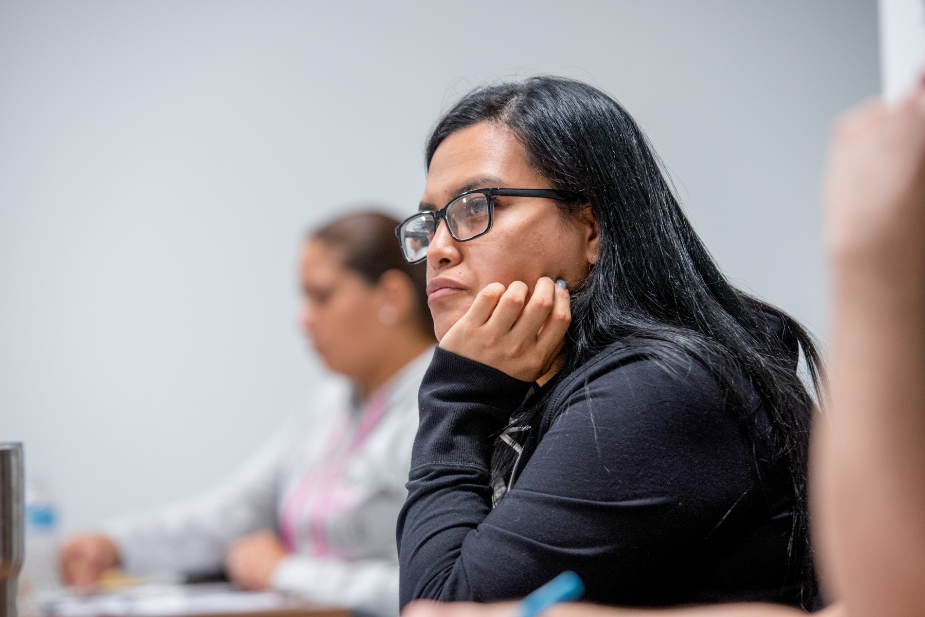 Female students with long black hair and glasses, hand on chin, looking forward, seated at desk, looking forward at instructor.