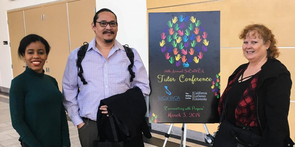 Three writing consultants stand next to poster for SoCal Writing Centers Association Tutors Conference 2018