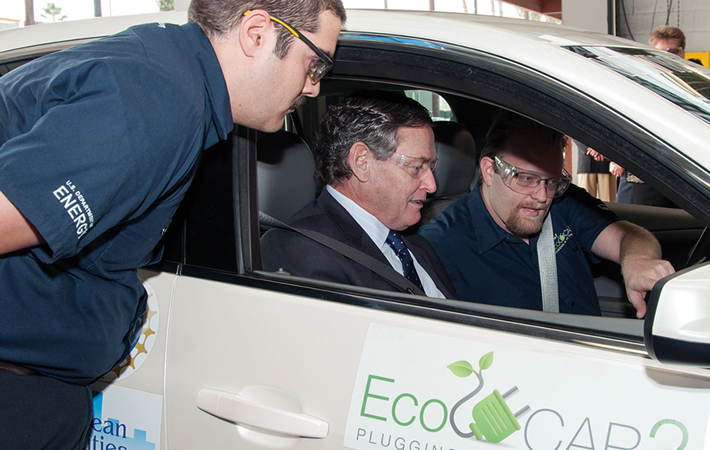 Christopher Reid, right, shows how the EcoCAR2 team records test results from the vehicle computers.