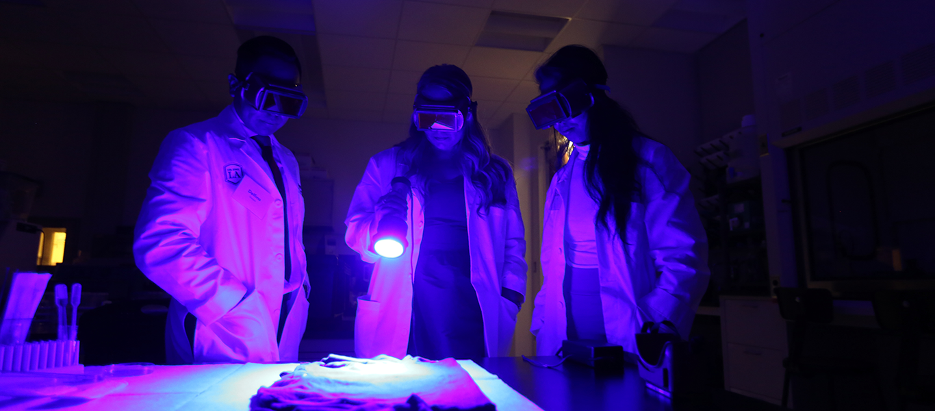 Criminalistics Students using a UV light to search for biological stains.