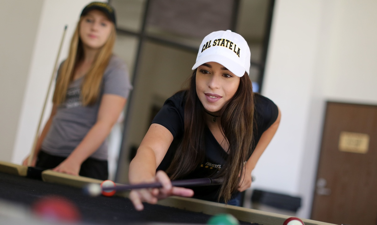 Two female residents playing pool.