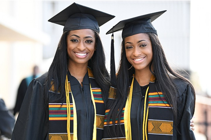 Two graduates in caps and gowns smiling