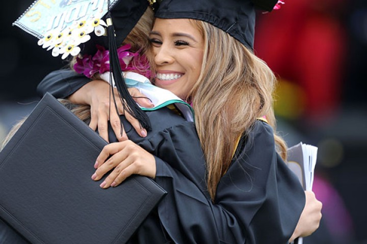 Graduates in caps and gowns hugging