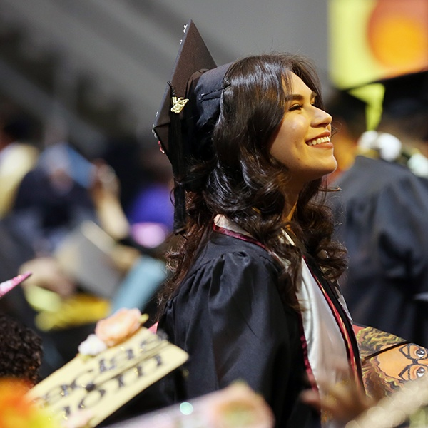 Graduating student in cap and gown smiles and looks in distance
