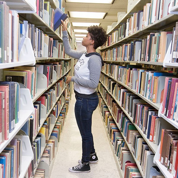 Student picking book from library shelf